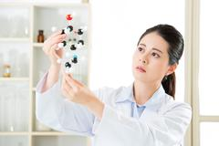 Asian female scientist looking at molecular model doing the science research Stock Photos