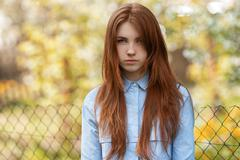 Young beautiful redhead woman with blurry background and chain-link fence - stock photo