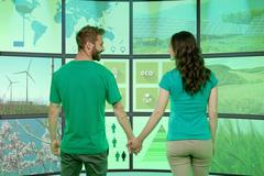 Young couple holding hands, standing in front of graphical screens, displaying - stock photo