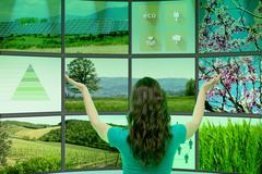 Young woman standing in front of graphical screens, displaying environmental Stock Photos