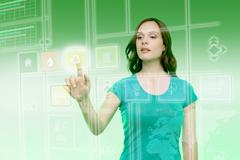 Young woman touching recycling icon on graphical screen Stock Photos