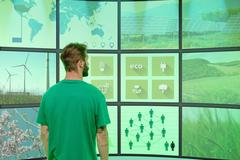 Young man standing in front of graphical screens showing environmental images, - stock photo