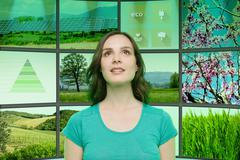 Portrait of young woman in front of graphical screens showing environmental Stock Photos