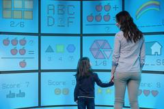 Mother and daughter standing in front of graphical screens showing educational Kuvituskuvat