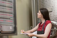 Young woman looking at control panel in wine cellar Stock Photos