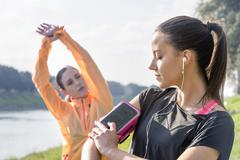 Young woman adjusting smartphone, attached to arm, for exercising - stock photo