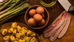 Overhead view of raw and prepared food, pasta, eggs and asparagus - stock photo