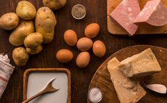 Overhead view of raw and prepared food, parmesan, milk, eggs and potatoes - stock photo