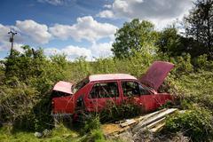 Abandoned open red car on wasteland - stock photo