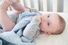 Portrait of blue eyed baby boy lying in crib with comfort blanket Stock Photos
