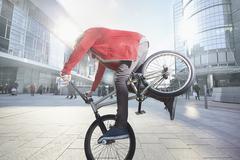 BMX Biker doing stunt in urban area Stock Photos