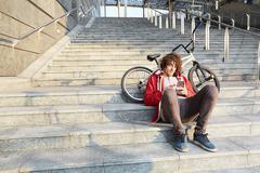 Man sitting on steps with BMX using smartphone Kuvituskuvat