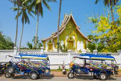 Colorful tuk-tuks in front of Haw Pha Bang temple on the grounds of the Royal Stock Photos