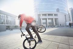 BMX Biker doing stunt in urban area - stock photo