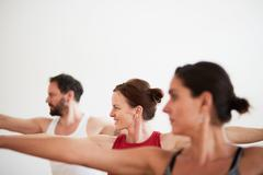 People in exercise studio arms open in yoga position Stock Photos
