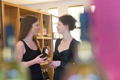 Sales assistant in wine shop recommending bottle of wine to customer Stock Photos