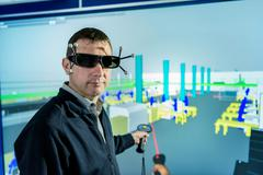 Portrait of engineer with factory graphic in 3D in virtual reality suite - stock photo