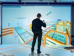 Engineer inspecting factory layout in 3D in virtual reality suite - stock photo