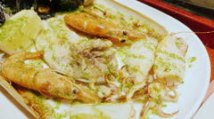 Close-up - eat seafood. On a plate the knife cuts the mollusk Stock Footage