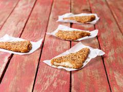 Food, fish, super seeded lightly dusted cod on painted red wooden table Stock Photos