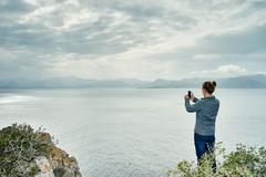 Young man standing on cliff photographing with smartphone, Alcudia, Majorca, - stock photo