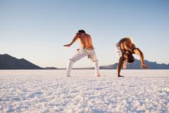 Surface level view of two men performing capoeira on Bonneville Salt Flats, Kuvituskuvat