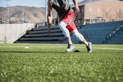 Neck down view of young man running doing agility training with markers on Stock Photos