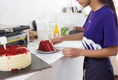 Waitress slicing red velvet cake at cafe counter - stock photo