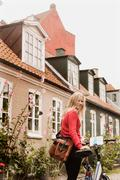 Woman pushing bicycle past houses, Aarhus, Denmark Stock Photos