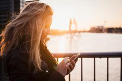 Woman using mobile phone at sunset, Spree River, Berlin, Germany Stock Photos