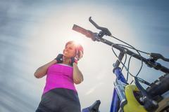 Woman with mountain bike putting her helmet on, Canton Wallis, Switzerland - stock photo