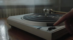 A man puts on a vinyl record and starts the gramophone - stock footage