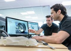 Engineers work with CAD design imagery in racing car factory Kuvituskuvat