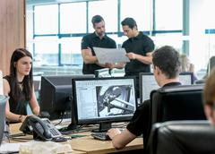 Engineers work with CAD design imagery in racing car factory - stock photo