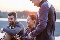 Group of friends, wearing sports clothing, chatting, outdoors - stock photo
