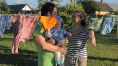 Parents play with a cute baby boy. Near the beautiful baby clothes drying Stock Footage