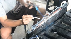 Thai people use lead and gas welding for fix and solder radiator of car Stock Footage