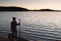 Mid adult woman standing at waters edge, looking across lake Stock Photos