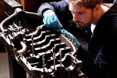 Male mechanic analysing car engine, stripped from car Stock Photos