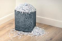 Overflowing shredded paper in paper shredder basket - stock photo