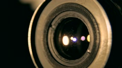 Lens of old retro style camera rounding in the dark in the lights studio Stock Footage