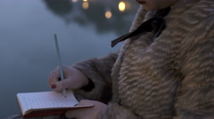Pensive young woman writes her thoughs on diary near the river Stock Footage