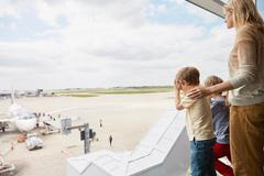 Mother and sons looking out of airport window - stock photo