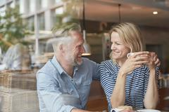 View through window of mature couple in coffee shop face to face smiling - stock photo