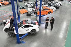 Engineer repairing racing cars in racing car factory - stock photo