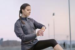 Young woman, wearing sports clothing, looking at activity tracker Stock Photos