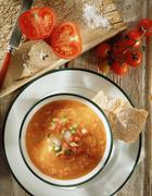 Gazpacho soup with crusty ciabatta bread, freshly cut tomatoes on the vine and - stock photo