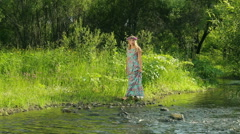 Young beautiful woman with flower wreath at the river. A beautiful girl walks by Stock Footage