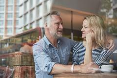 View through window of mature couple in coffee shop chatting Stock Photos