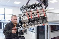 Engineer assembling engine in racing car factory Stock Photos